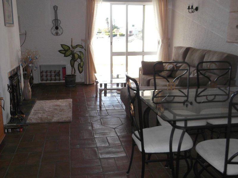 Lounge and dining area with patio doors leading to the terraced balcony.