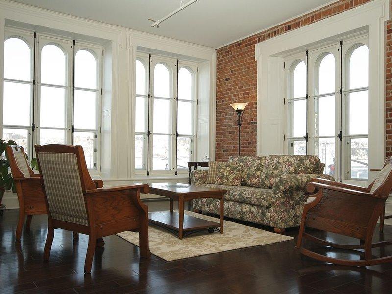 A bela sala de estar com tectos altos e janelas.