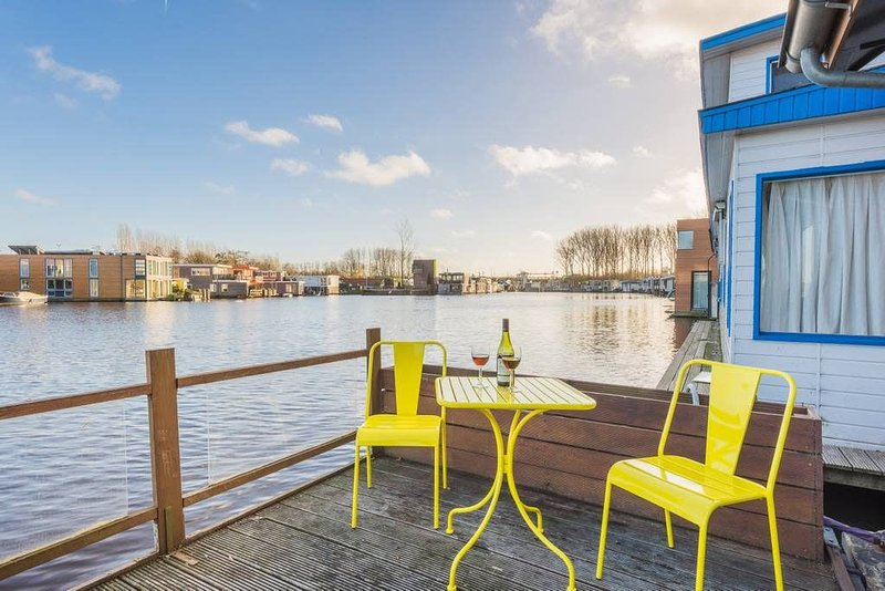 Houseboat studio with canal view and bikes, aluguéis de temporada em Amsterdã