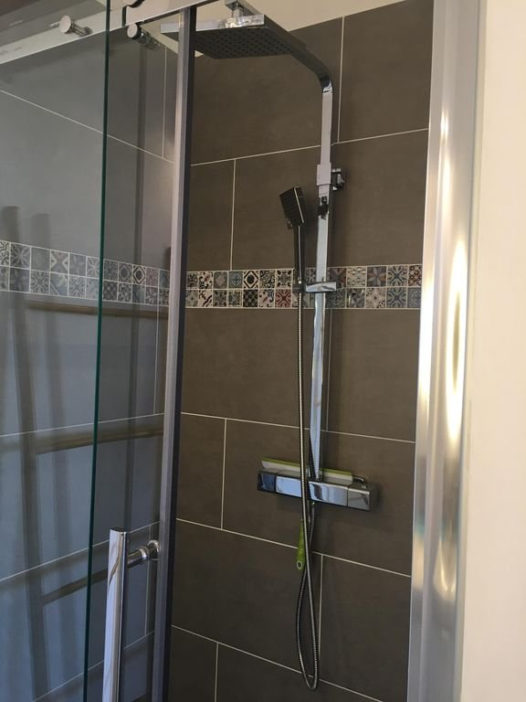 the shower of the bathroom of the small room