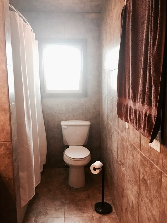 Baño en la planta baja con combinación de ducha / bañera, inodoro y lavabo