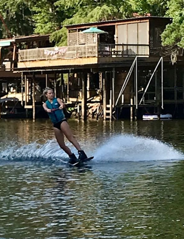 wake boarding on the river. Off the Hook house in the back ground