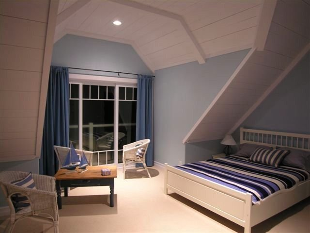 Bedroom suite with private bathroom, sitting area, and balcony