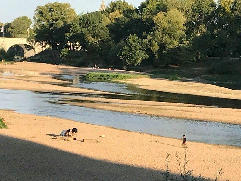 A gauche, le pont Wilson et le long de la Loire, des personnes se prélassant