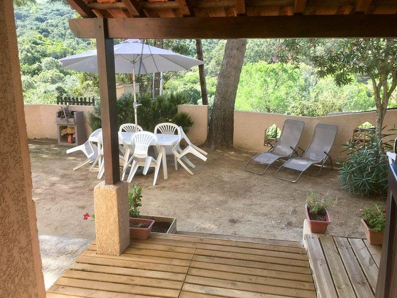 Zona exterior: jardín con barbacoa, mesa y sombrilla.