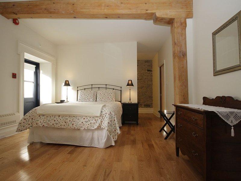 El dormitorio con una cama queen size, vestidor y baño en suite.