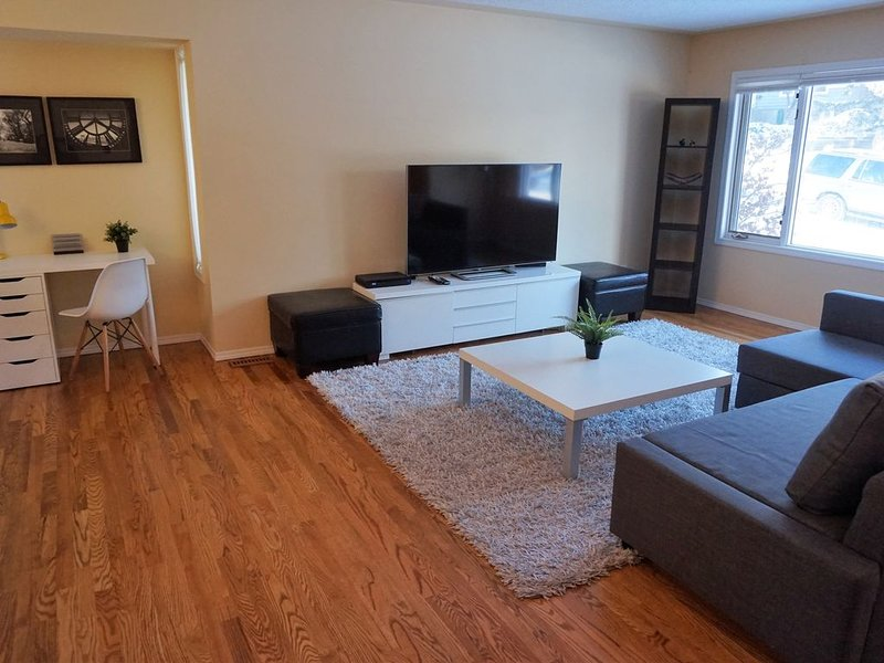 Spacious and open living room with large, bright windows and beautiful hardwood
