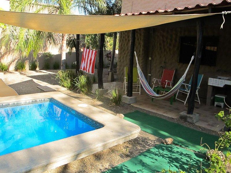 Área de estar com piscina e sombra