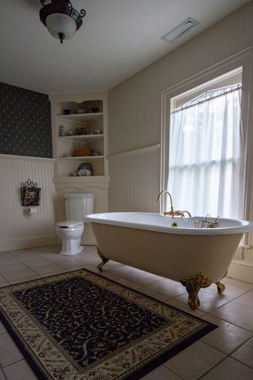 Salle de bain attenante avec baignoire sur pieds et douche à vapeur dans la chambre 1