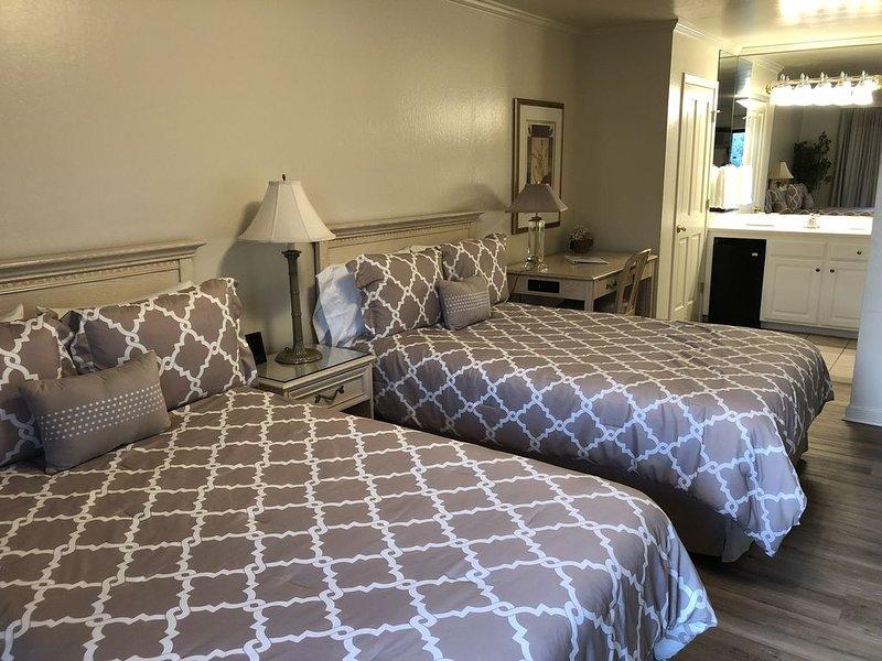 Chambre avec 2 lits doubles et un bureau et une vanité à l'arrière.