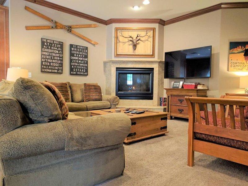 Espace de vie rustique raffiné avec de nombreux sièges, grand écran, câble et foyer au gaz.