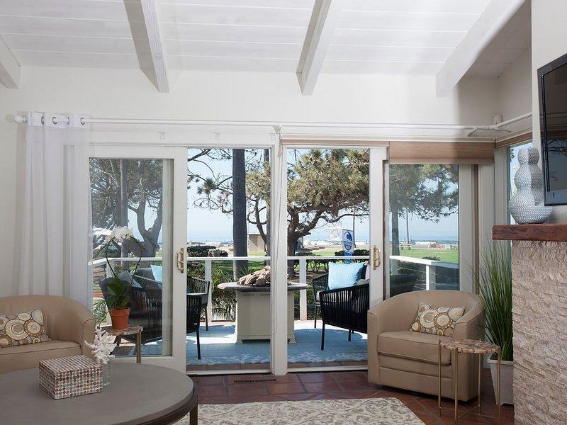 Salon donnant sur un balcon d'un côté, avec foyer donnant sur l'océan