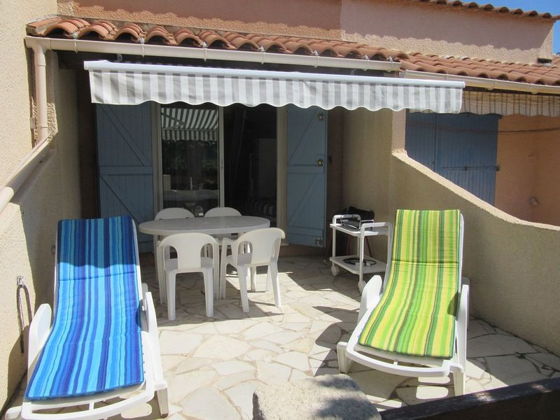 Terrace with garden furniture, awning, deckchairs.