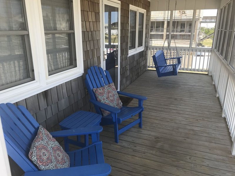 Cozy screened-in porch with all-weather chairs and swing!