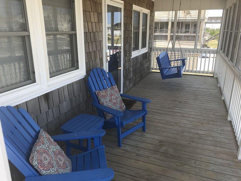 Acogedor porche con sillas para todo clima y columpios.