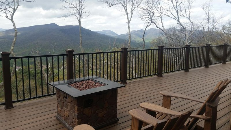 Expansive deck with 10 chairs, gas fire pit, and a picnic table.