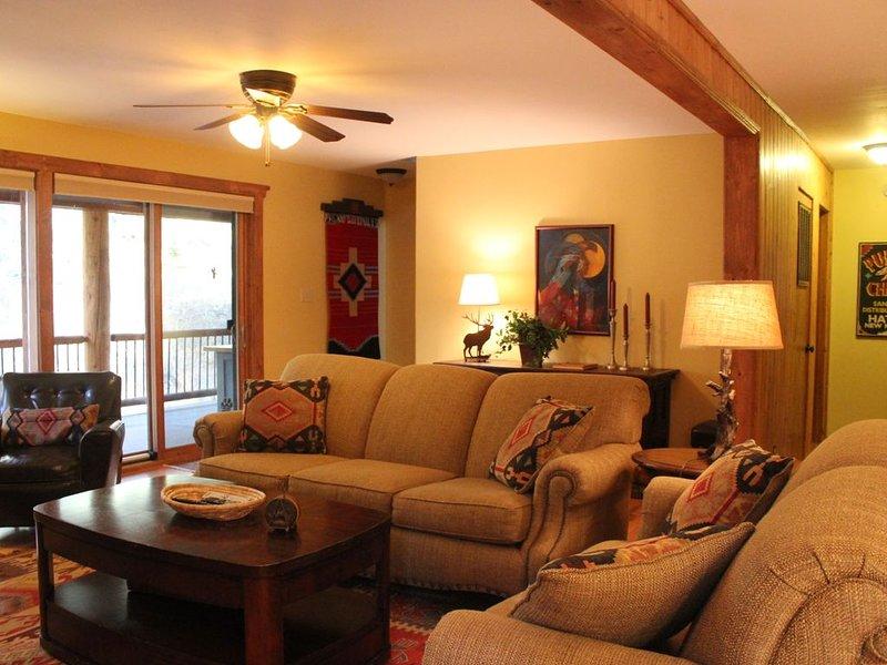 Living room w/ Fireplace, TV & veiw of river