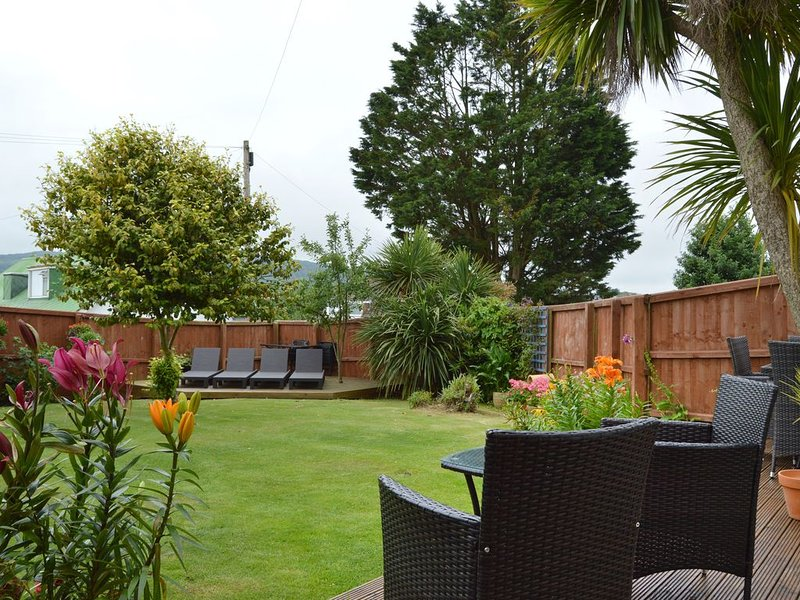 Looking down the garden, to sundeck  with comfortable loungers.