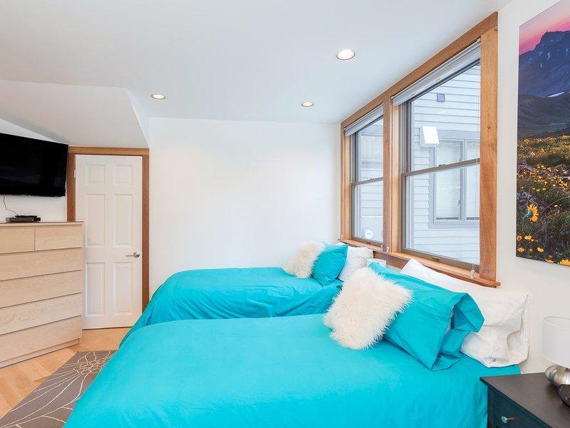 Guest bedroom features desk, flatscreen TV & closet.