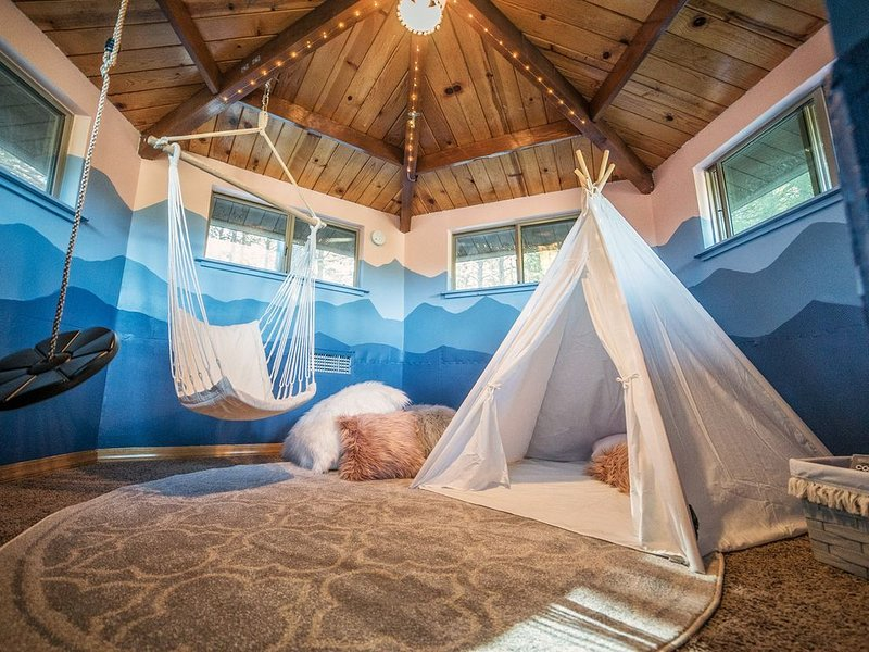 Kids play area featuring a tee pee and suspended seating.