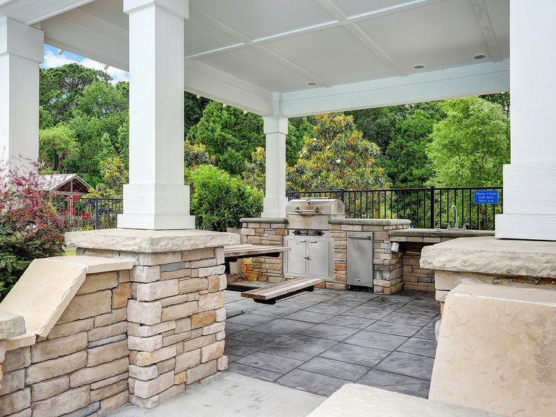 Outdoor grilling area overlooking pool, lake and gazebo