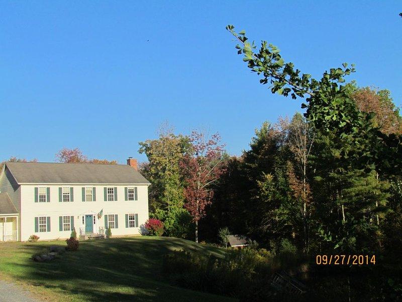 Façade de la maison - par beau soleil du soir, entouré de bois.