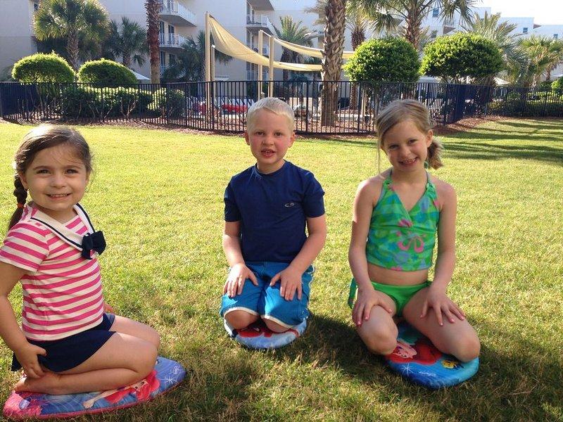 Niños jugando afuera del patio en la zona de césped.
