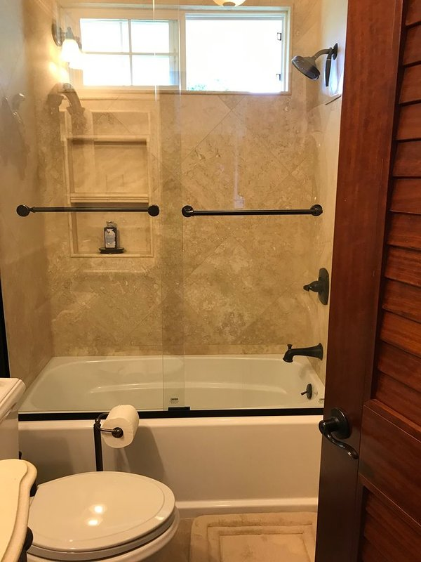 Glass-enclosed tub and shower.