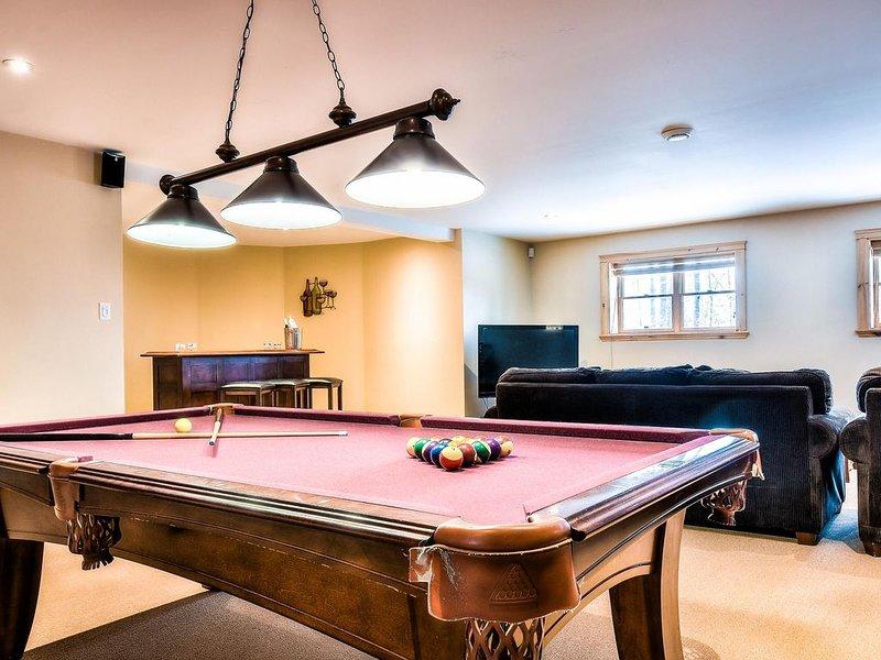 Grand sous-sol avec table de billard, bar sec et espace de vie.