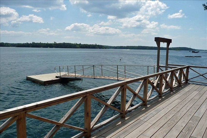 Large deck with a dock at water's edge