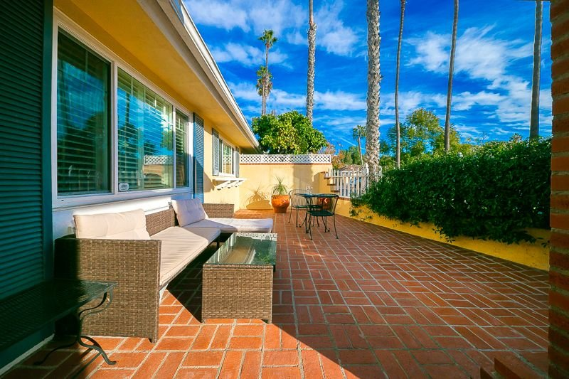 Front patio to the right of the entrance has  comfortable seating, a barbecue and a table for al fresco dining.