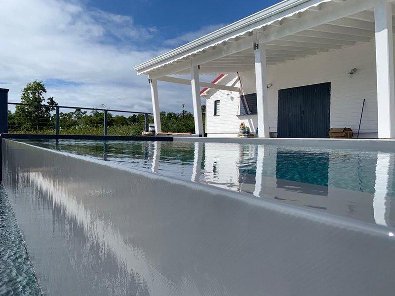 Villa Paruline avec piscine à debordement   et sa  grande terrasse avec vue mer, vakantiewoning in Grand Bourg