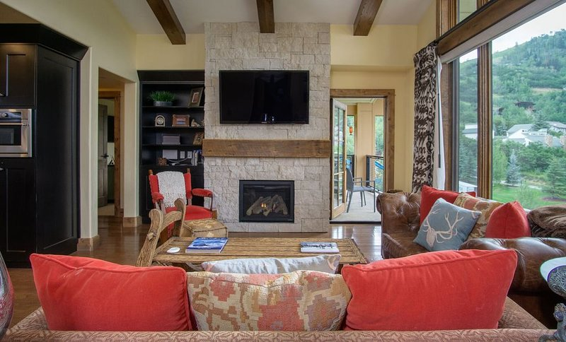 Window Door to the Porch, Sofas, Arm Chair, Coffee Table, TV, and Fireplace.
