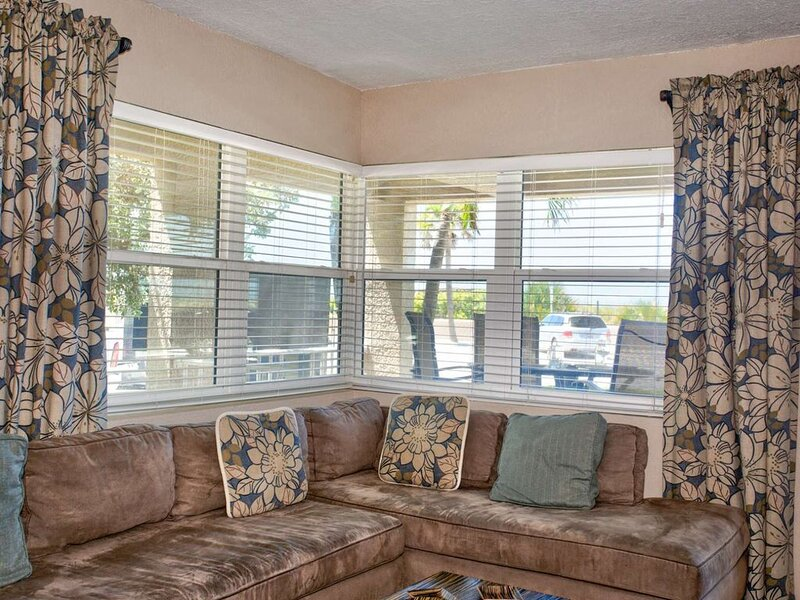 The living room has a water  view and a large couch.