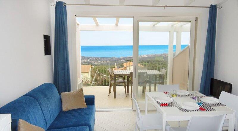 Attrezzato bilocale con incantevole vista mare, piscina in comune e lavatrice, holiday rental in Isola Rossa