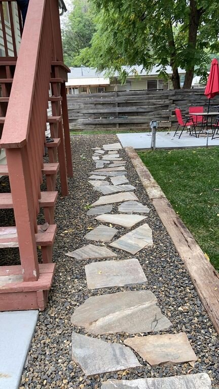 Flagstone walking path in back yard leading to bbq patio.