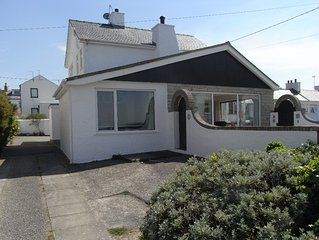 Bright modern holiday cottage steps from the beach and in the heart of village