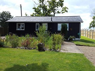 Logcabin/bungalow in superb rural location overlooking the River Hundred valley.