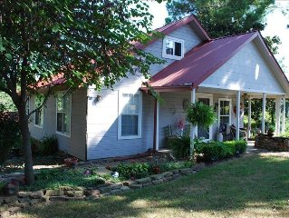 A charming old farm house sitting under a 100 yr. old magnolia tree in.