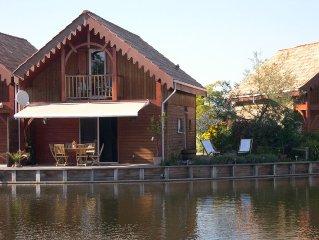 Maison bois au bord d'un plan d'eau et proche du lac d'Hourtin.