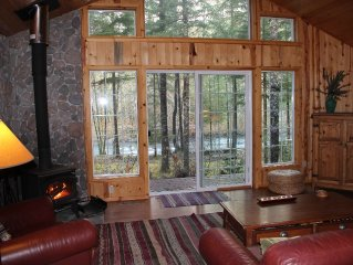 Living room with woodstove and views of the river