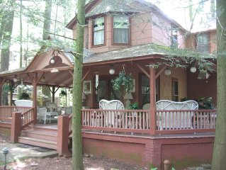 Stately Victorian Cottage With Wrap Around Porch Situated On A Walking Street.