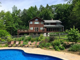 Mountain retreat with heated pool and wrap around deck by Red Cottage Inc.