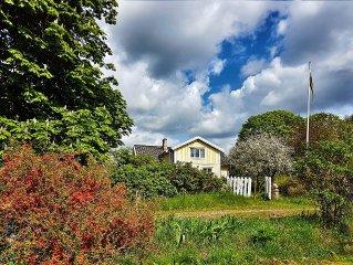 Schones gelbes Holzlandhaus im Garten von Sweden 'Smaland'. Village Troxhult.