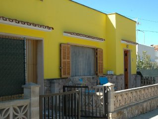 Una casa amarilla cerca del azul del mar