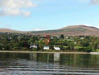 Strandhaus in Templenoe an Kenmare Bay in County Kerry mit Garten am Wasser.