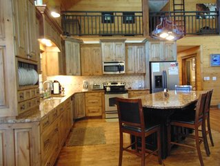 Kitchen with refrigerator, stove/oven, microwave, dishwasher, and beverage cooler.