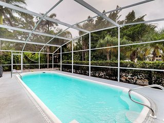 Canal-front home with private dock, covered lanai with heated pool and grill