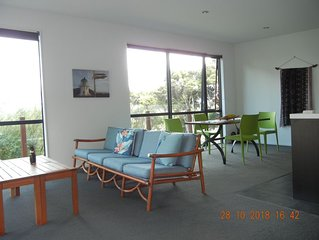 Holiday house with sea views over tall totara.