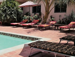 Large room with single beds and sofa in Bed  & Breakfast  with large pool